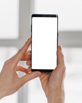 Manos de primer plano sosteniendo smartphone
