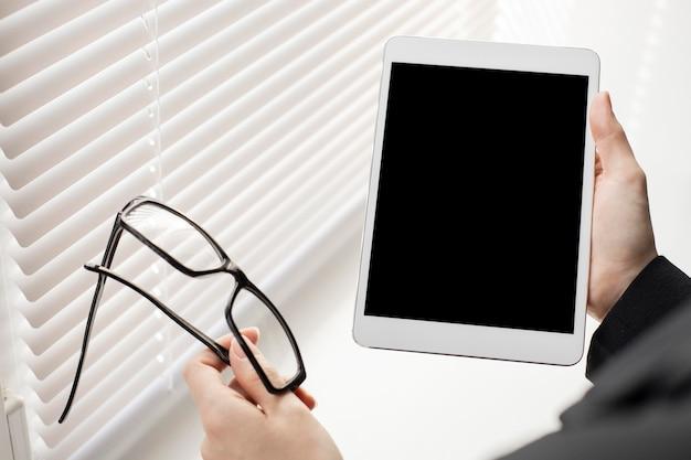 Manos de primer plano sosteniendo la tableta