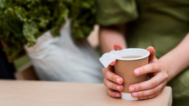 Manos de primer plano sosteniendo una taza de té orgánico