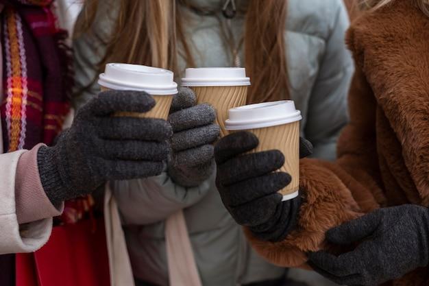 Manos de primer plano sosteniendo tazas de café