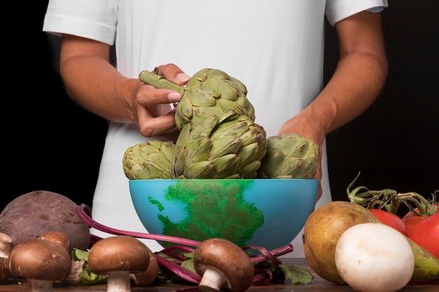 Manos de primer plano sosteniendo vegetales