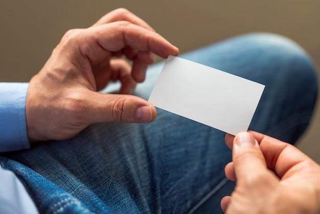 Manos de primer plano con tarjeta blanca
