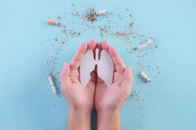 Las manos protegen los pulmones del cigarrillo en la pared azul claro. deja de fumar. día mundial sin tabaco.