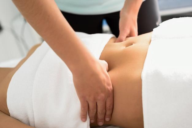 Manos que dan masajes al abdomen femenino. terapeuta que aplica la presión en el vientre.