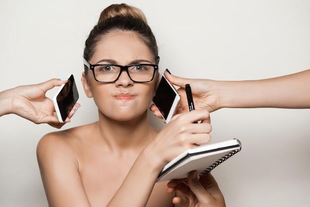 Manos que dan los teléfonos a la empresaria hermosa joven que sostiene el cuaderno