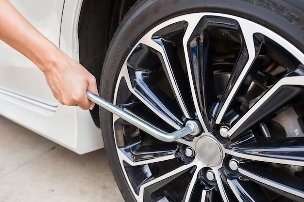 Manos que desmontan una rueda de automóvil moderna (llanta de acero) con una llave de tuercas para cambiar la rueda