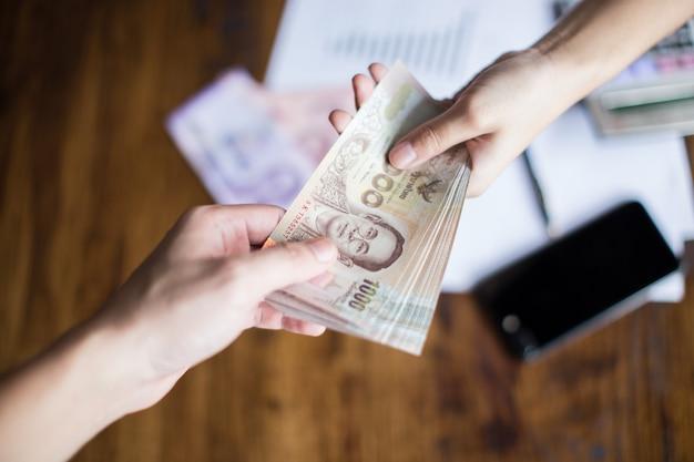 Manos que están entregando dinero para ganancias comerciales