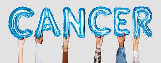 Las manos que muestran la palabra globos de cáncer