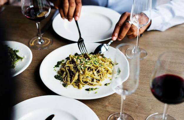 Manos que sostienen el cuchillo y el tenedor obteniendo comida del plato