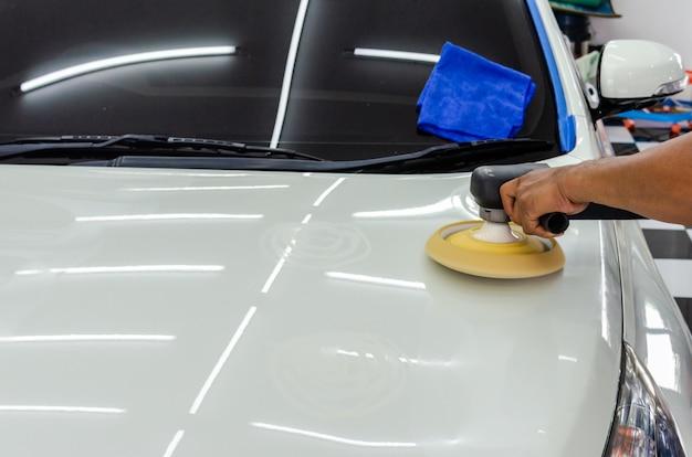 Las manos que sostienen la herramienta de trabajo pulen el coche.