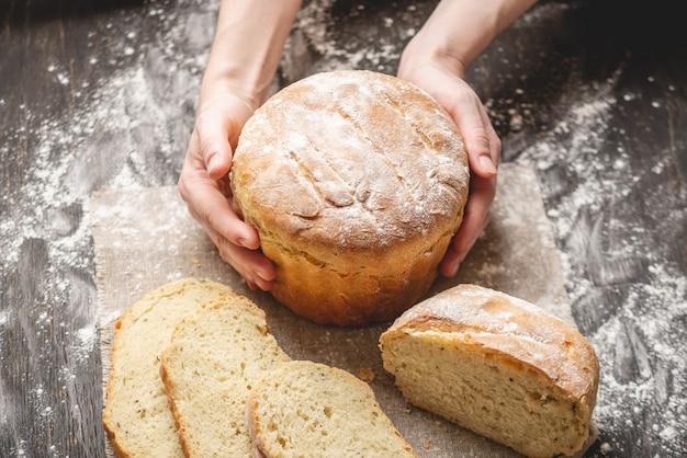 Manos que sostienen el pan fresco natural hecho en casa con una corteza de oro en un de madera viejo. productos de panadería y repostería.