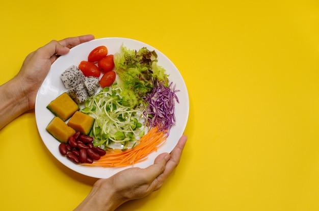 Manos que sostienen una placa de la ensalada del vegano en fondo amarillo.