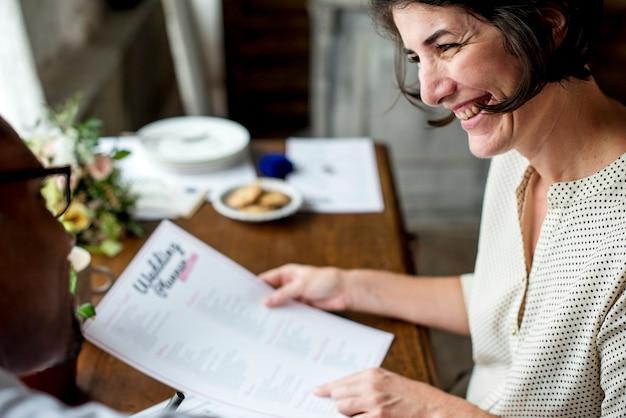 Manos que sostienen la planificación de la boda lista de verificación información preparación