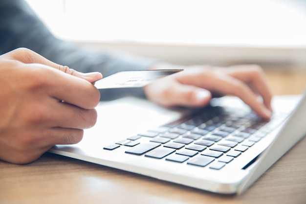 Manos que sostienen la tarjeta de crédito y escribiendo en la computadora portátil