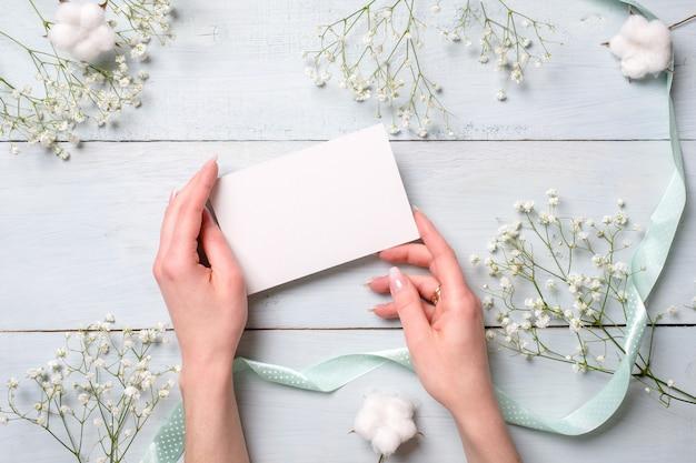 Manos que sostienen la tarjeta de papel en blanco en el escritorio de madera azul claro con las flores.