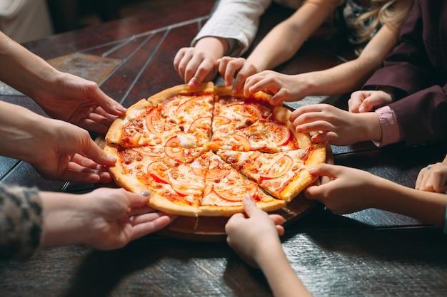 Manos que toman las rebanadas de la pizza de la tabla de madera, visión ascendente cercana.