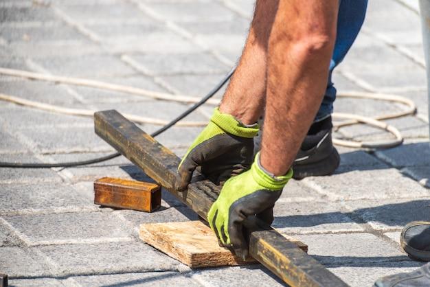 Las manos que trabajan bajan una tubería de metal cerca de una construcción