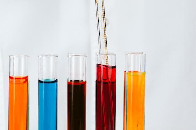 Manos de químico sosteniendo tubos de ensayo con líquidos y haciendo experimentos