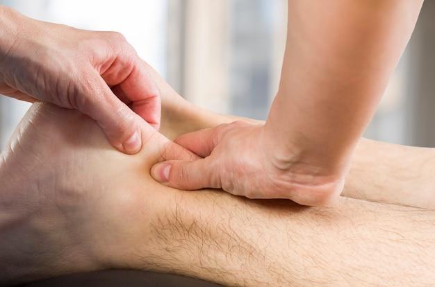 Manos de quiropráctico, fisioterapeuta haciendo masaje muscular de la pantorrilla al paciente hombre. osteópata