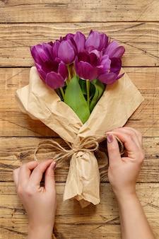Manos con ramo de tulipanes morados en papel artesanal en la vista superior de la mesa de madera