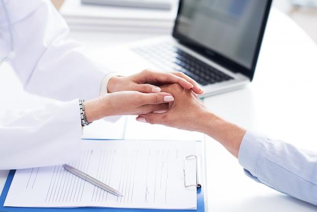 Manos recortadas del médico consolando a un paciente irreconocible