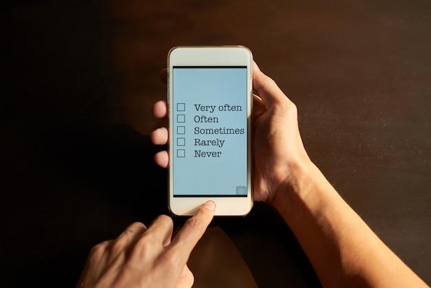 Manos recortadas que completan la encuesta en línea en la pantalla táctil del teléfono inteligente