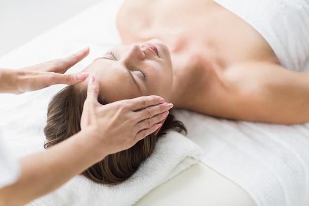 Manos recortadas de terapeuta realizando reiki en mujer
