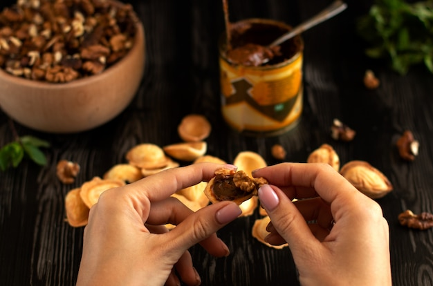 Las manos reúnen galletas en forma de nueces con leche condensada y nueces en una mesa de madera oscura con verduras