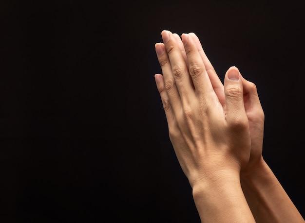 Manos rezando en el fondo oscuro con fe en la religión y creencia en dios.