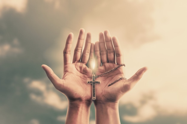 Las manos rezando sostienen un crucifijo o una cruz de collar de metal con fe en la religión y creencia en dios