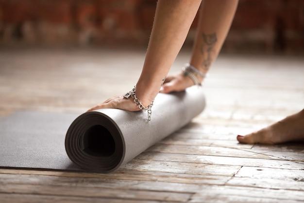 Las manos rodando estera de fitness concepto de estilo de vida saludable