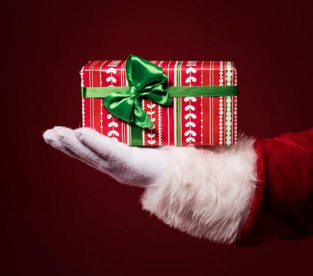 Manos de santa claus sosteniendo una caja de regalo sobre fondo rojo.