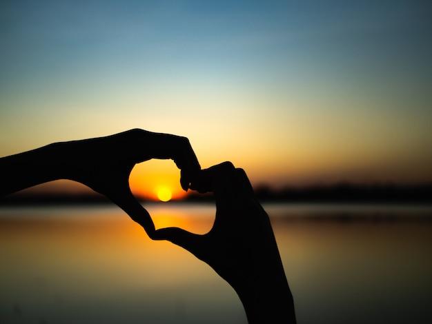 Las manos de la silueta para ser forma del corazón en fondo de la puesta del sol.