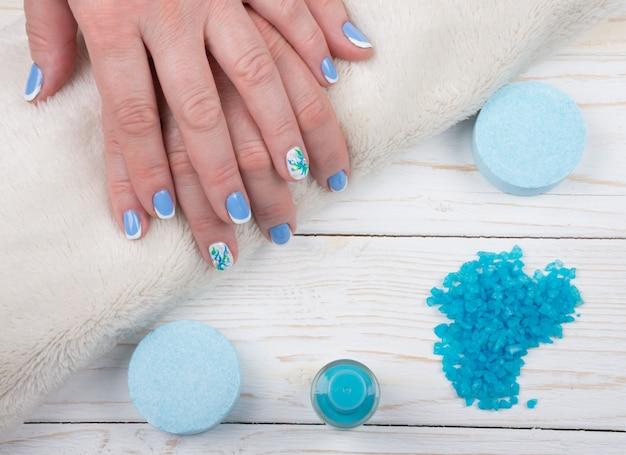Manos sobre una toalla, sal de baño y una botella de esmalte de uñas