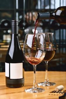 Las manos del sommelier en el marco ofrecen y vierten vino en una copa de vinificación.