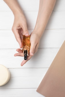 Manos sosteniendo aceite corporal sobre fondo blanco de madera