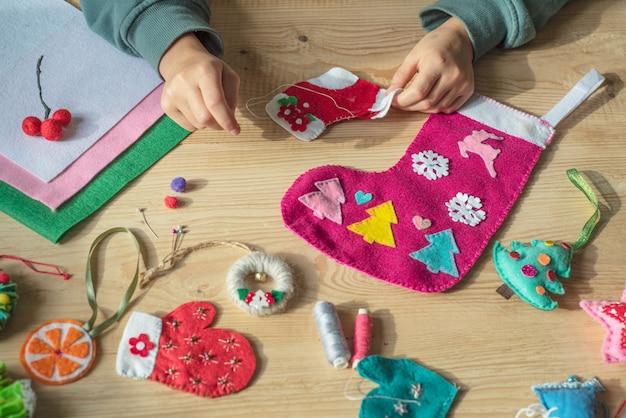 Manos sosteniendo la aguja y coser fieltro calcetín navideño para decoración navideña y año nuevo