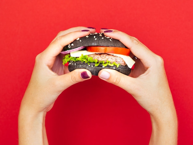 Manos sosteniendo apetitosa hamburguesa con fondo rojo.