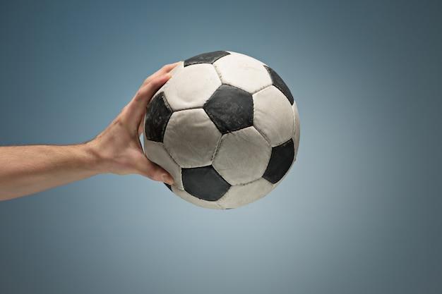 Manos sosteniendo el balón de fútbol
