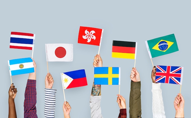 Manos sosteniendo banderas internacionales