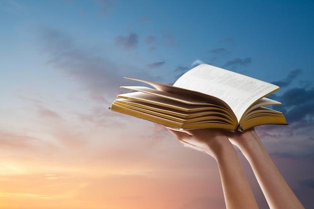 Manos sosteniendo la biblia sobre el cielo del atardecer