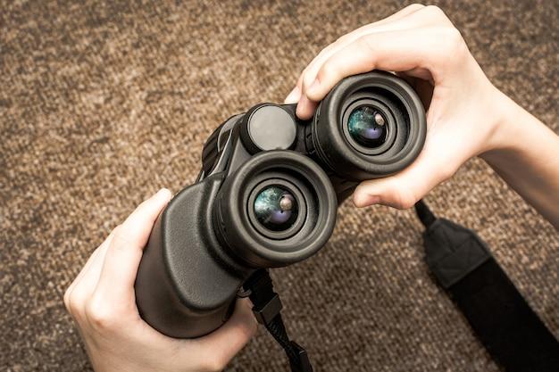 Manos sosteniendo binoculares