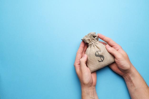 Manos sosteniendo una bolsa de dinero con espacio de copia