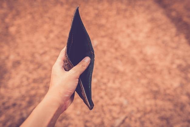Manos sosteniendo un bolso sin dinero.