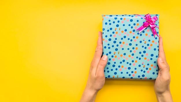 Manos sosteniendo caja de regalo envuelta de lunares con lazo rosa sobre fondo amarillo