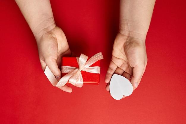 Manos sosteniendo caja de regalo y corazón de papel sobre fondo rojo.