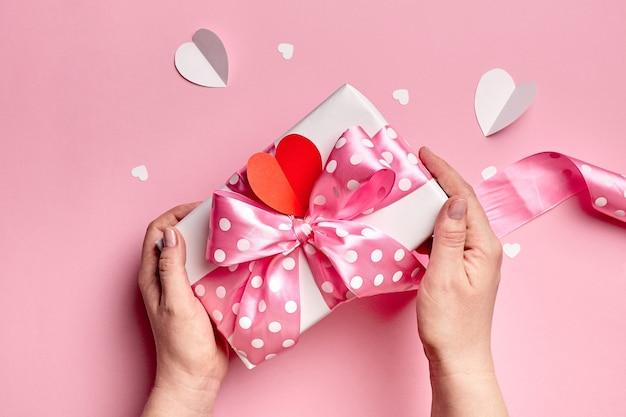 Manos sosteniendo la caja de regalo del día de san valentín con corazones de papel sobre fondo rosa