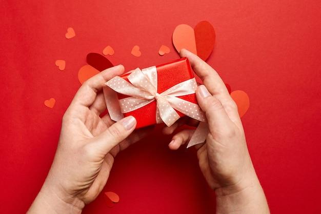 Manos sosteniendo la caja de regalo del día de san valentín sobre fondo rojo con corazones de papel