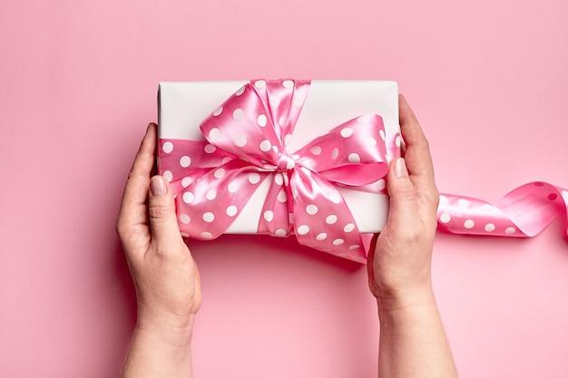 Manos sosteniendo caja de regalo con lazo grande sobre fondo rosa