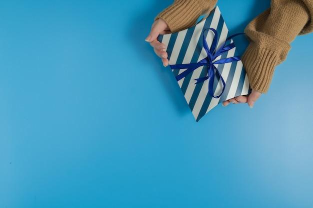 Manos sosteniendo una caja de regalo de rayas azules y blancas atadas con una cinta sobre fondo azul.